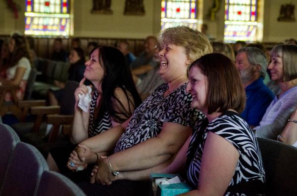 Kindergarten and first grade teacher Jen Owczarzak, aide Teri Neetz and second and third grade teacher Sandy Goik laugh and cry during a photo slideshow following Holy Trinity Catholic School