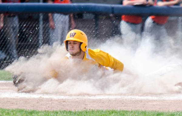 Bay City Western junior David Fegan slides into home plate during Division 1 regional finals at Saginaw Valley State University on Saturday, June 7. Bay City Western won and will proceed to the quarterfinal game at Central Michigan University on June 10. (Danielle McGrew | The Bay City Times)