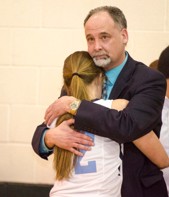 Bay City All Saints Assistant Coach Mike Debo hugs his daughter, senior Katie Debo, as she leaves the court from her final high school basketball game at the regional tournament at Akron-Fairgrove High School on Tuesday, March 4. (Danielle McGrew | The Bay City Times)