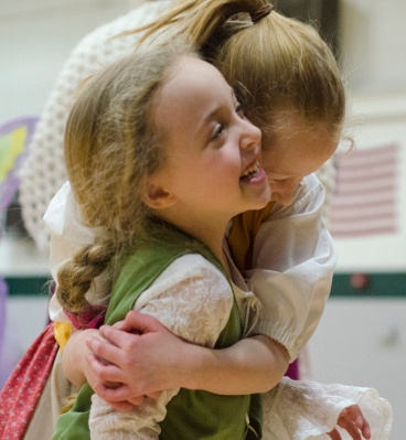 Lorin Summers, 5, giggles as Kaydence Merso, 7, hugs her before a rehearsal for My Son Pinocchio at Pinconning High School on Friday, March 28. (Danielle McGrew | The Bay City Times)