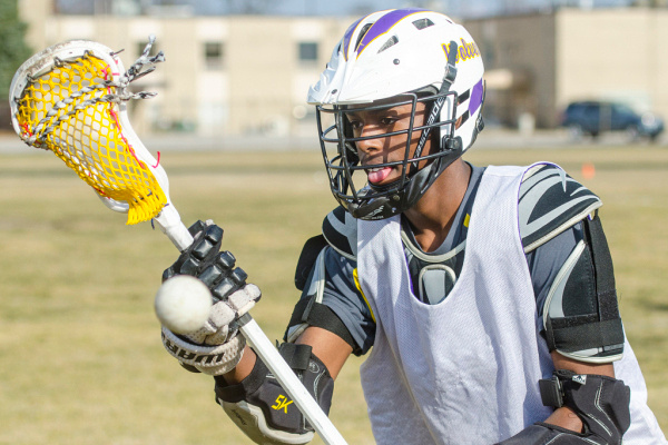 Sophomore Ramarkiss Williams warms up tossing and catching a ball before a lacrosse scrimmage against Wolves alumni on Tuesday, April 8, at Bay City Central. (Danielle McGrew | The Bay City Times)