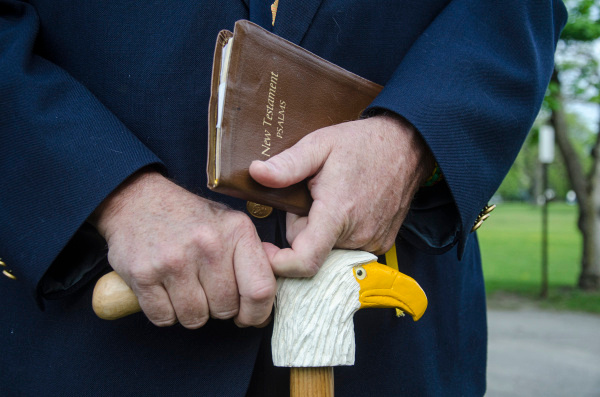 Kenneth Burtch, 10th District Commander for the American Legion, holds a Bible and grasps a custom-made cane following a Memorial Day ceremony at Oak Ridge Cemetery on Monday, May 26. (Danielle McGrew | The Bay City Times)