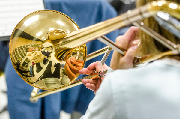 Fellow musicians are reflected in a trombone player