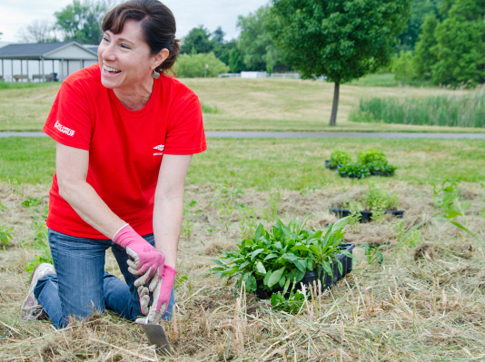 """Dow Chemical employee Sheila Gombar-Fetner of Midland plants native species at Discovery Preserve on Euclid Avenue in Bay City on Monday. Gombar-Fetner, a Midland County Master Gardener, was one of 84 employees helping the Saginaw Basin Land Conservancy transform the area into an urban nature preserve. """"This is the kind of volunteering I like to do,"""" she said, adding that it applies to her work in the environmental sustainability department as well."""