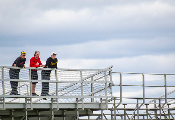 A trio of spectators watches the Bay City Western-Central baseball game from the football bleachers in Auburn on Friday, May 16. (Danielle McGrew | The Bay City Times)