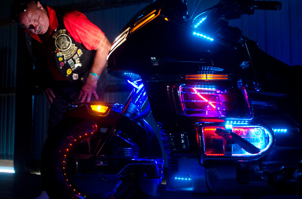 """Jim Lust of Crestline, Ohio, examines a motorcycle owned by K.C. Glad of Temperance, Mich., during a light competition at the Gold Wing Road Riders Association Rally at the Midland County Fairgrounds on Saturday, Aug. 2.  Glad said the bike has about 2,000 lights on it, and he adds a little more each year. """"I get a lot of looks off it,"""" he said. """"Kids love it."""""""