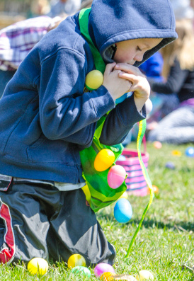 A child struggles to hold so many plastic eggs during the Redeeming Love Christian Embassy Easter Egg Hunt at Nate Doan Park on Bay City
