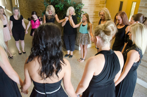 Contestants and pageant crew gather in a circle to pray before the Miss Bay County pageant on Sunday, July 20, at Garber High School in Essexville. (Danielle McGrew | for the Bay City Times)