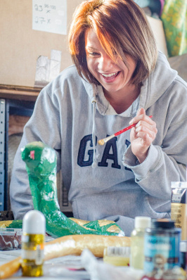 Meghan Jurek laughs as she tries to paint a diamond pattern on a paper mache snake in the Meagher's garage in Hampton Township on March 8. The Meagher's float will be in this year's St. Patrick's Day Parade. (Danielle McGrew | The Bay City Times)