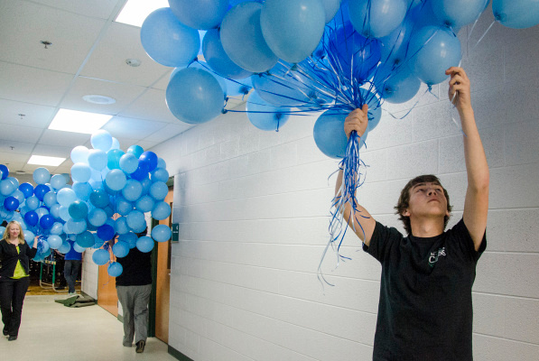 Senior Derek Daniels gathers balloons to be released in memory of Pinconning sophomore Kirsten Hughes, who passed away in November, at Pinconning High School on Wednesday, May 15. (Danielle McGrew | The Bay City Times)