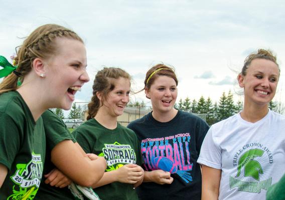 Sophomore Kayla Gauthier, freshman Brianna Foltz, senior MacKenzie Maxon and junior Gabby Yanoski chat before practice at Pinconning High School on Tuesday, May 13. (Danielle McGrew | The Bay City Times)