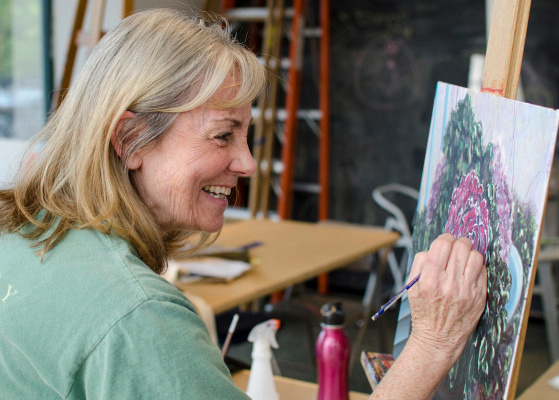 Mellisa Boyd laughs while painting a cauliflower plant at Studio 23 in downtown Bay City on Tuesday, May 20. (Danielle McGrew | The Bay City Times)