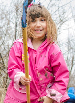 Caitlin Hyde, 5, dumps soil from her shovel while planting winterberry bushes during a Saginaw Bay Land Conservancy event at Discovery Park in Bay City Friday, April 25. (Danielle McGrew | The Bay City Times)
